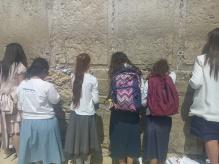 Mädchen vor der Klagemauer. Man schreibt seine Gebete auf Zettel und steckt sie in die Ritzen zwischen den Steinen.